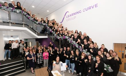 Learning Curve Group staff celebrating their IIP Gold award, with Brenda McLeish CEO.